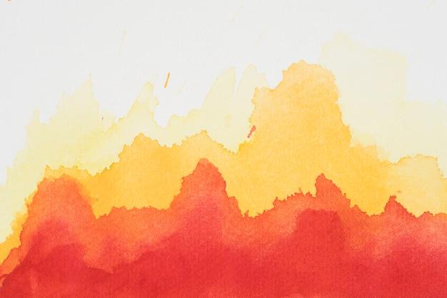 Красная и желтая смесь красок на белой бумаге