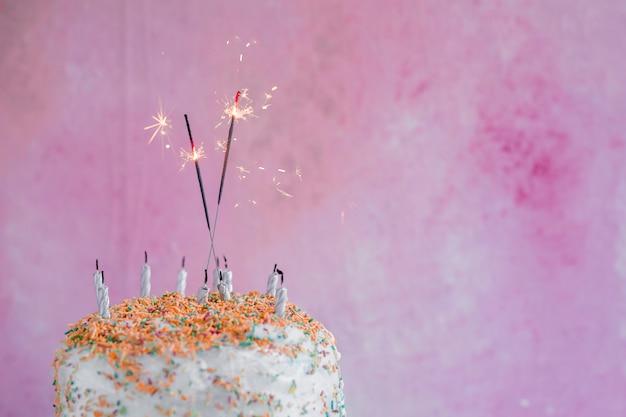 スパークラーとパステルカラーの誕生日ケーキ