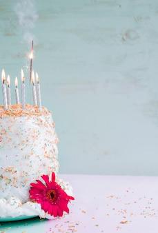水彩の背景の前に誕生日ケーキ