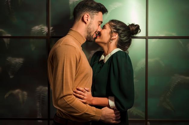 壁の近くに陽気な女性にキスする幸せな人