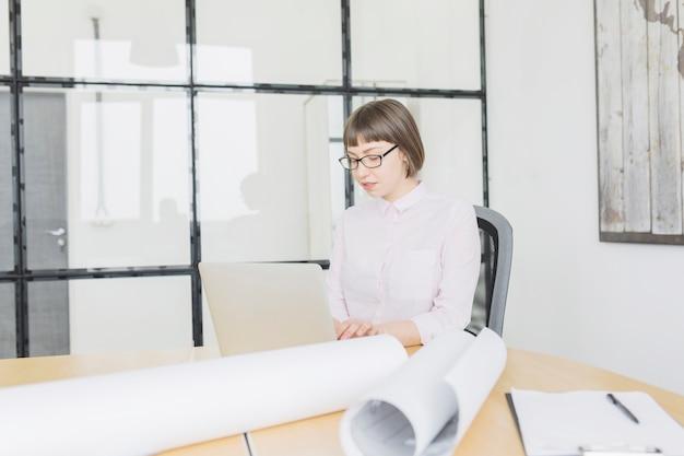 Коммерсантка работая с компьтер-книжкой в офисе