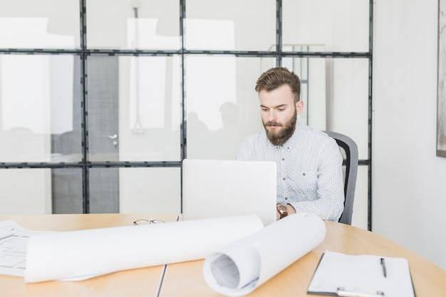 Бизнесмен работает с ноутбуком в офисе