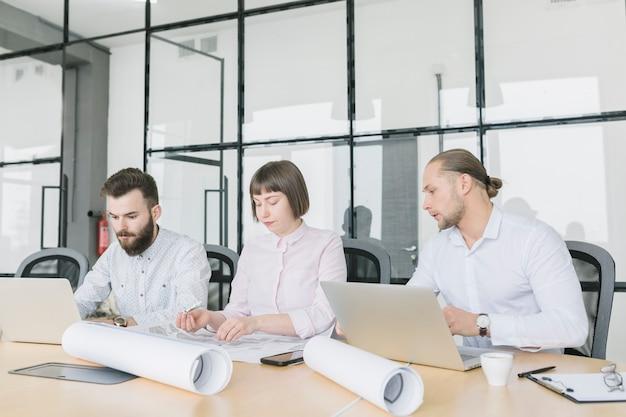 Деловые люди, работающие с ноутбуком в офисе