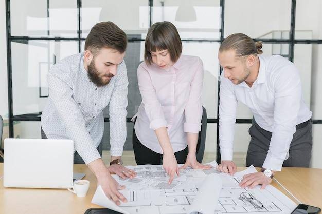 Деловые люди, глядя на планы в офисе