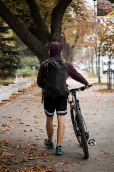 公園でバイクを持つフィットネス少年