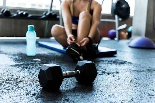 Фитнес-девушка завязывает шнурки