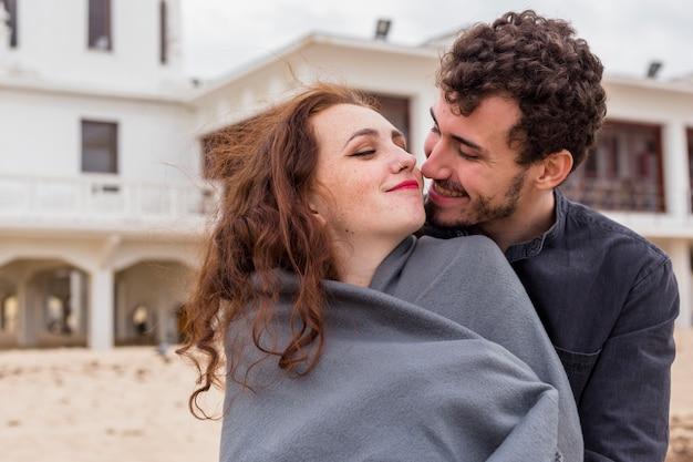 毛布の中で女性を抱擁している若い男