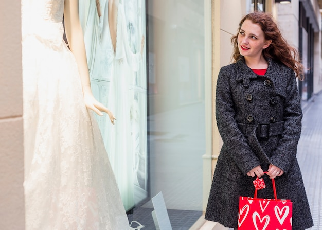 店の窓でウェディングドレスを見ている女性