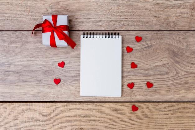 メモ帳とテーブルに赤い心の小さなギフトボックス