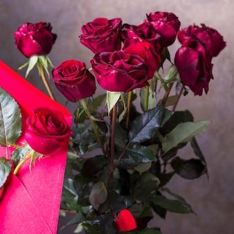 灰色の背景に赤いバラの花束