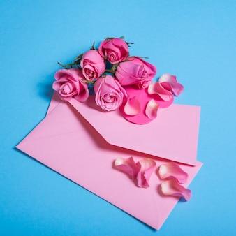 青のテーブルに封筒とピンクのバラ