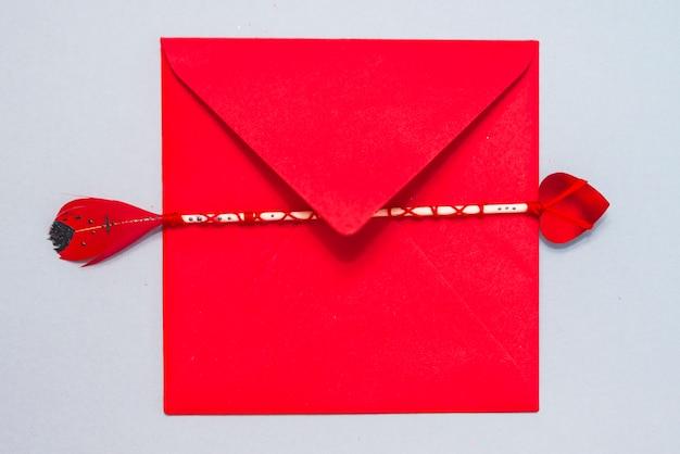 テーブル上に赤い封筒とラブの矢印