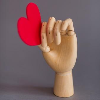 テーブルに赤い心を抱く木製の手