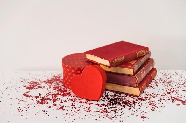 Книги возле подарка и украшение сердца на столе