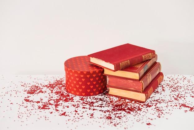 Куча книг рядом с подарком на столе