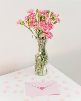 Букет цветов в вазе возле конверта и бумажных сердечек на столе