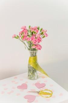 Букет цветов в вазе с лентой возле ножниц и бумажных сердечек
