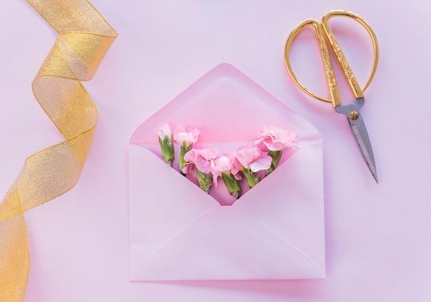 テーブル上の封筒にピンクの花