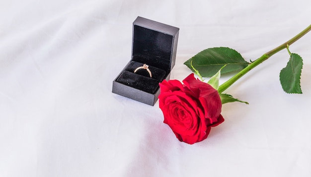 白いテーブルにバラの結婚指輪