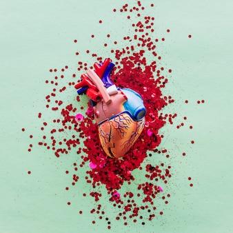テーブルの上のスパンコールと小さなプラスチック製の人間の心
