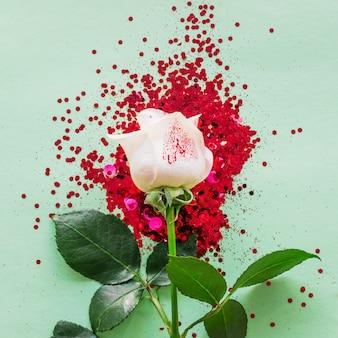 テーブルの上のスパンコールと白いバラ支店