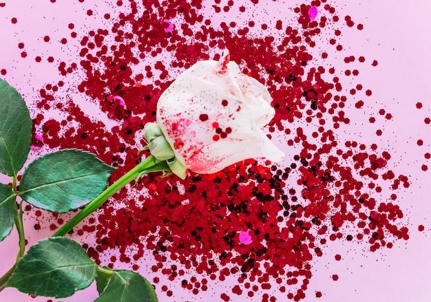 ピンクのテーブルの上のスパンコールと白いバラ支店