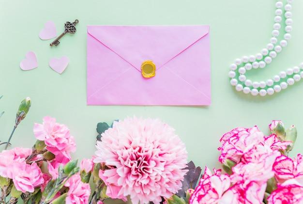 緑色のテーブル上の封筒と異なるピンクの花