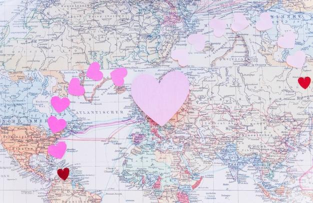 世界地図上の小さなカラフルな紙の心