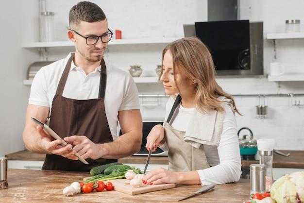 家庭でタブレットを使って料理するカップル