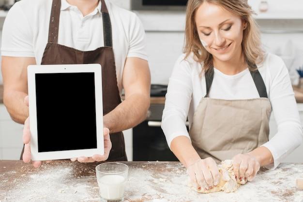タブレットで調理するカップル