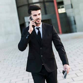 彼の携帯電話を使用してオフィスビルの前にビジネスマン