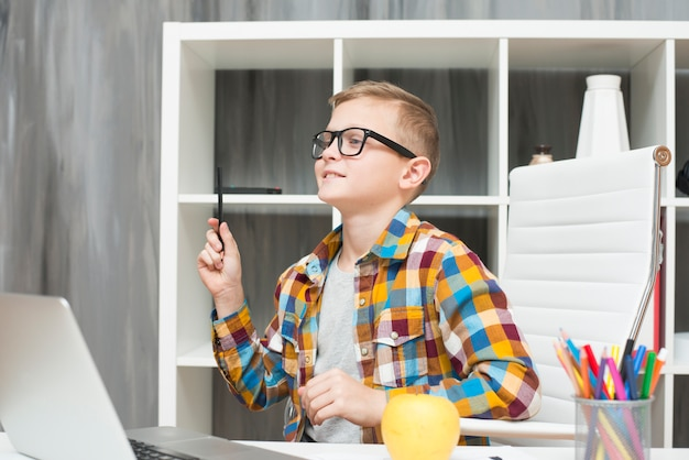 デスクでノートパソコンを持っている男の子