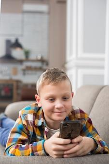 スマートフォンを使ったソファーの男の子