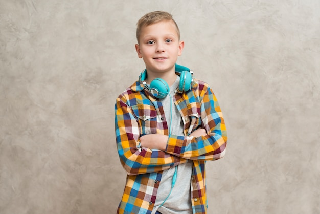 首の周りのヘッドホンを持つ少年の肖像