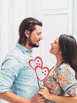 Пара держит бумажные сердечки на деревянной палочке