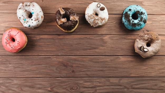 木製の背景にカラフルなドーナツ