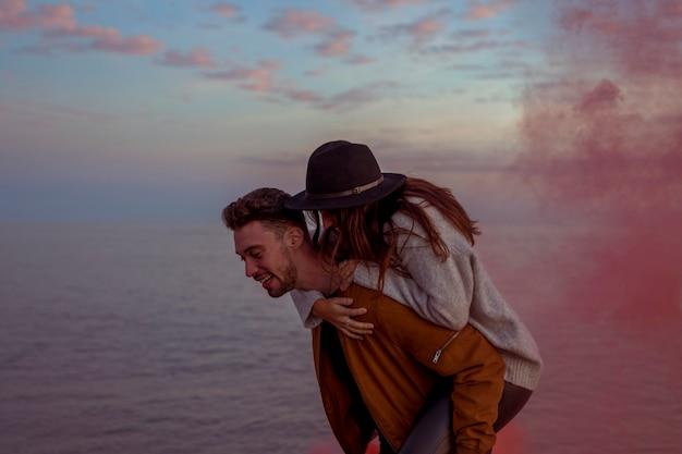 Мужчина держит женщину на спине на берегу моря