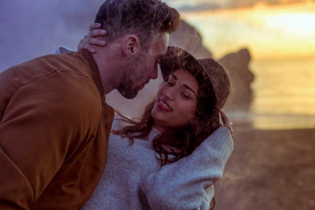 Мужчина обнимает женщину на берегу моря