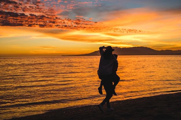 Мужчина держит женщину на спине на берегу моря ночью