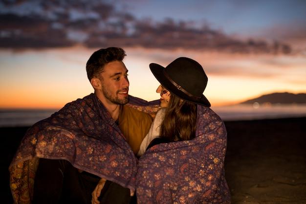 海岸で笑っている毛布の若いカップル