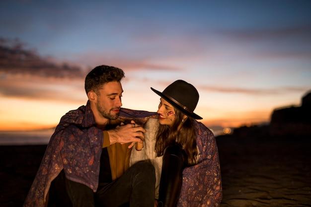 海岸に手を持って毛布の若いカップル
