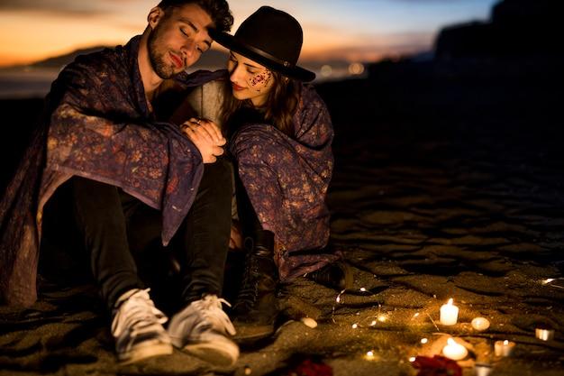 Милая пара в одеяле, сидя на берегу моря
