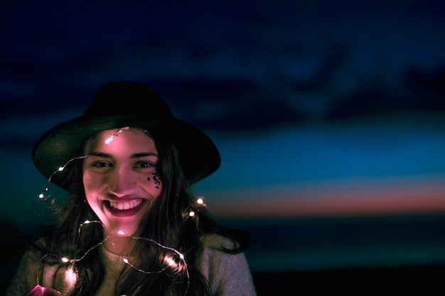 Счастливая женщина с горящей гирляндой на голове