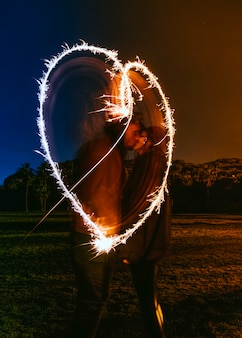 Пара, целующаяся около сердца, рисующего от бенгальских огней на темной улице