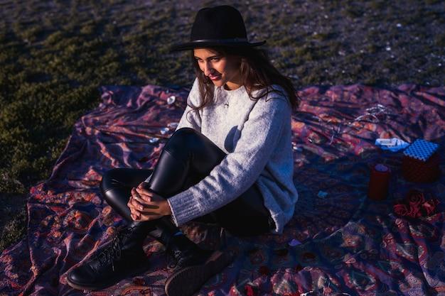草の上の掛け布団の上に座っているきれいな女性