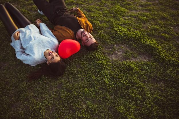赤いハート形風船と草の上に横たわる若いカップル