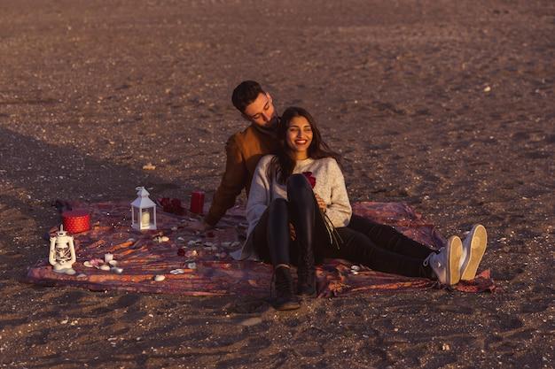 海岸の掛け布団の上に座っている若いカップル