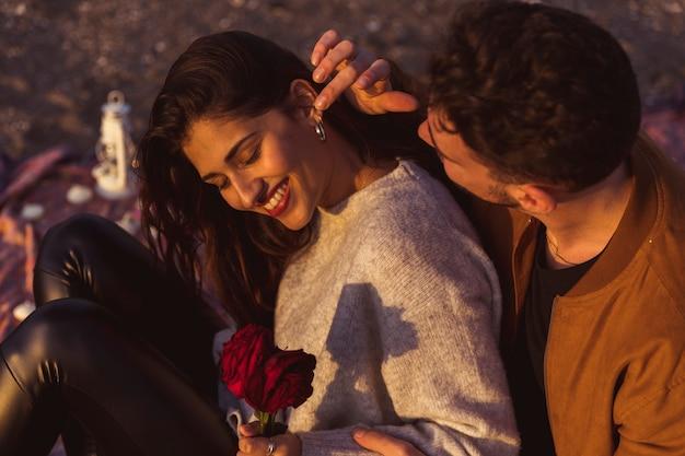 バラを持つ女性の耳に触れる若い男