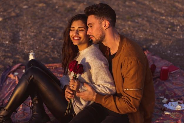 掛け布団に赤いバラを持つ男ハグ女性