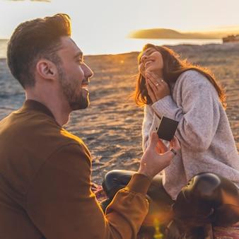 Молодой человек делает предложение женщине на песчаном берегу моря